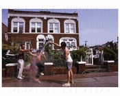 Family playing with water hose 1980's