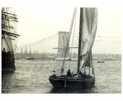 Brooklyn Bridge behind a sail boat