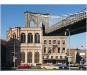 Brooklyn Bridge -  view of Brooklyn Tower emerging behind commercial buildings on the corner of Front Street & Camden Plaza