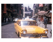 Classic Yellow taxi passing through Chinatown