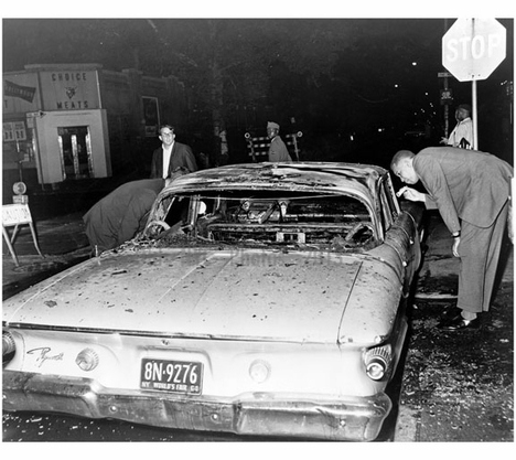 Detective examines burned out police car on Herkimer & Nostrand Ave in Bedstuy, after Harlem riots spread