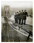 Men standing on Brooklyn Bridge under construction