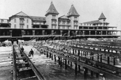 Ocean side view of Brighton Beach Hotel in process of being hauled back from the teeth of the ocean, 1888