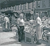Street peddler making a sale on Bleecker street at Morton, 1955