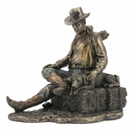 Bronze Cowboy and Dog Napping on a Bale of Hay Sculpture