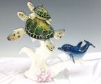 Two Green Turtles on Coral with a Dolphin Statue