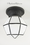 Cast iron porch ceiling fixture with octagon black lined globe, circa 1910s