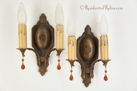 PAIR cast iron 2-candle wall sconces with amber glass drops, circa 1920s
