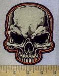 3685 N - Tan And Blackened Out Eyes -  Skull Face - Outlined In Orange - Embroidery Patch