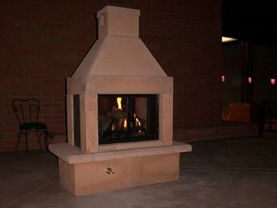 stone see through outdoor gas fireplace with gas logs and burner