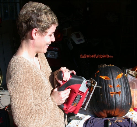 Here is Lisa cutting the flat black pumpkin