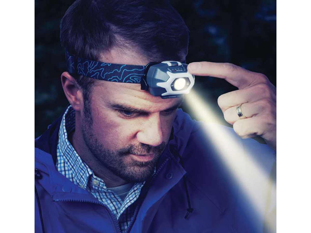Person click the powerswitch on Inova STS headlamp