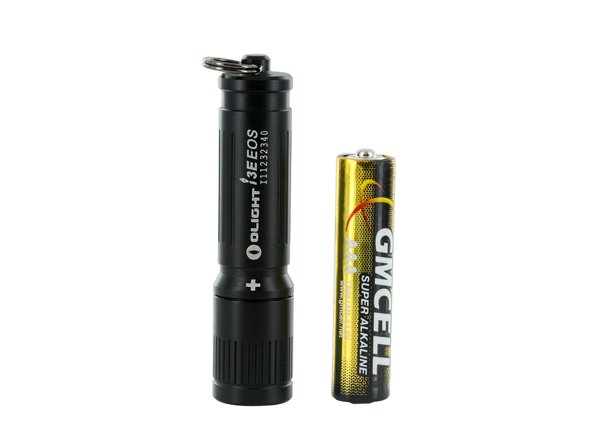 OLIGHT I3E EOS COMPACT FLASHLIGHT WITH INCLUDED BATTERY STANDING VERTICALLY NEXT TO IT