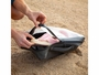 nite ize waterproof large packing cube putting sandy sneakers in cube on the beach