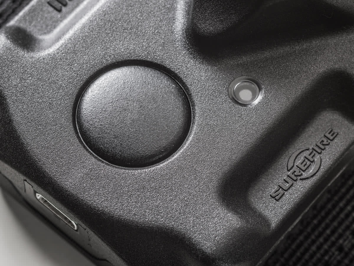 Black button on top of the tactical flashlight