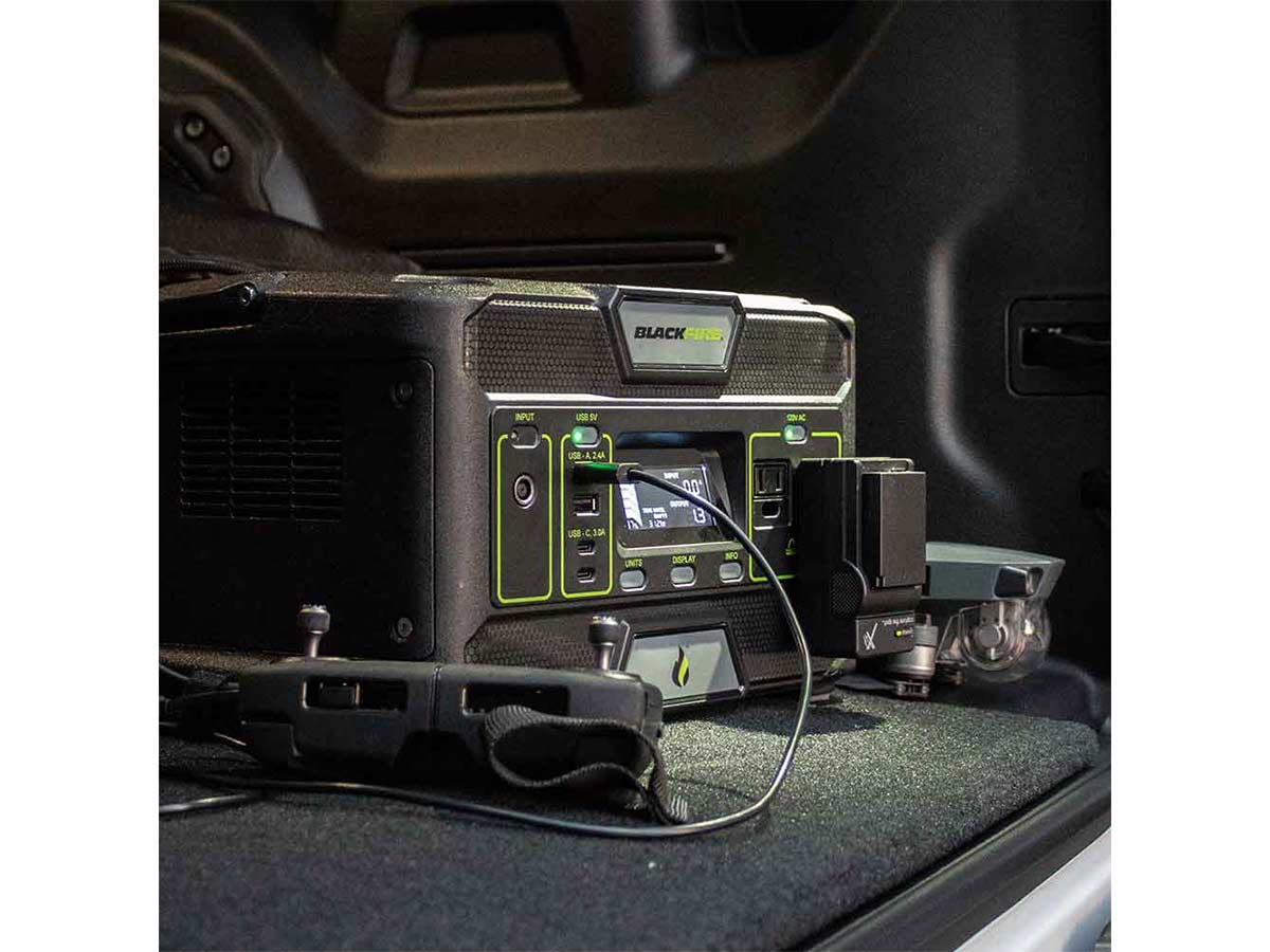 Blackfire PAC500 power station sitting in the back of a truck or sport utility vehicle with charging cords coming off of it