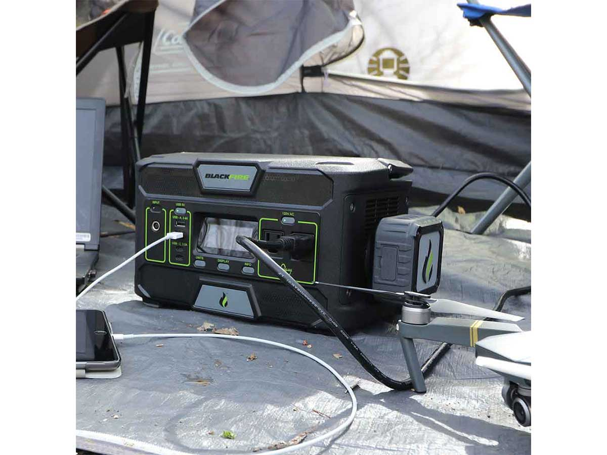 Blackfire PAC500 power station sitting on a tarp outside a tent with charging cables