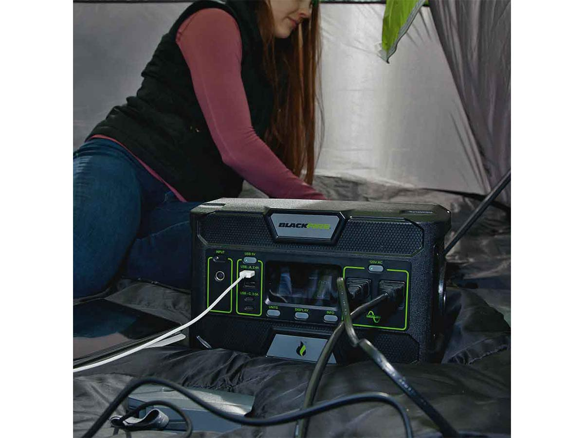 Blackfire PAC500 power station sitting inside a tent next to a camper with several devices plugged into it