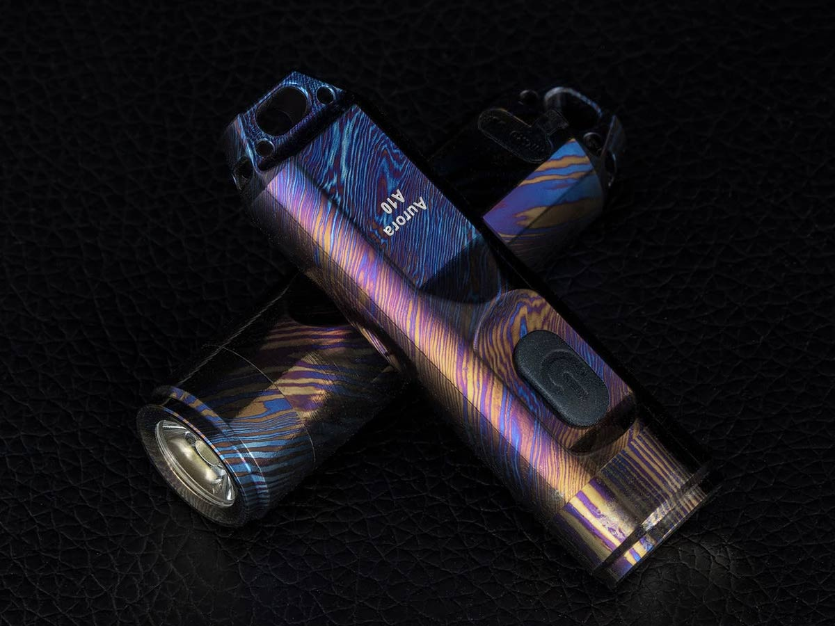 rovyvon a10 timascus flashlights, two, laying angled on top of one another on a leather surface