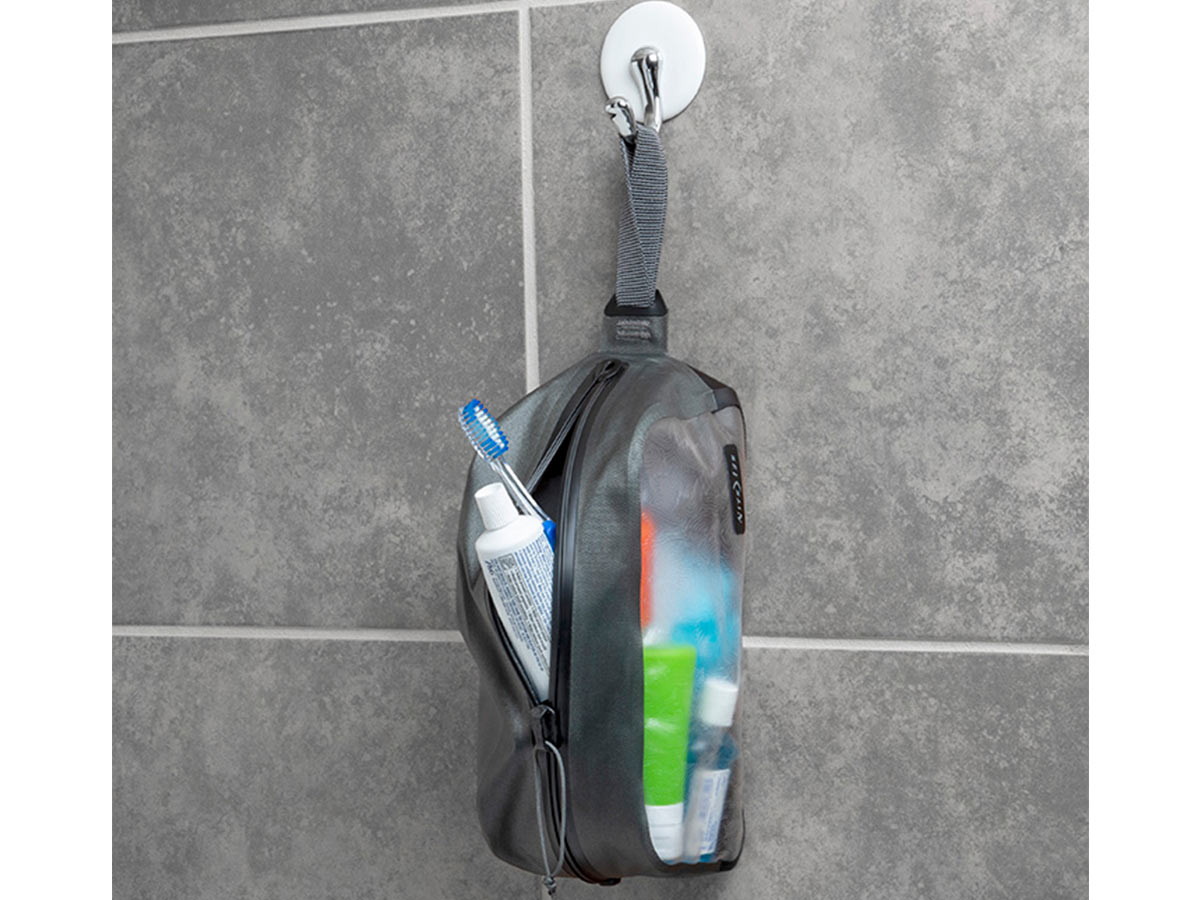 nite ize waterproof toiletry bag with contents hanging from handle in a shower without items falling out