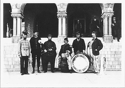 GROUP OF EARLY BAND MEMBERS CLOWNING ON STEPS OF ENCINA HALL, STANFORD UNIVERSITY, 1890'S SMALL POSTCARD