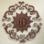 Beautiful iron wall grille with gold monogram to add a personalized touch to your home decor.