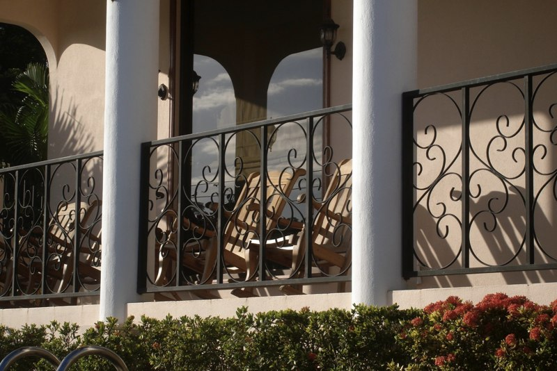 Four rocking chairs on front porch overlook the pool.