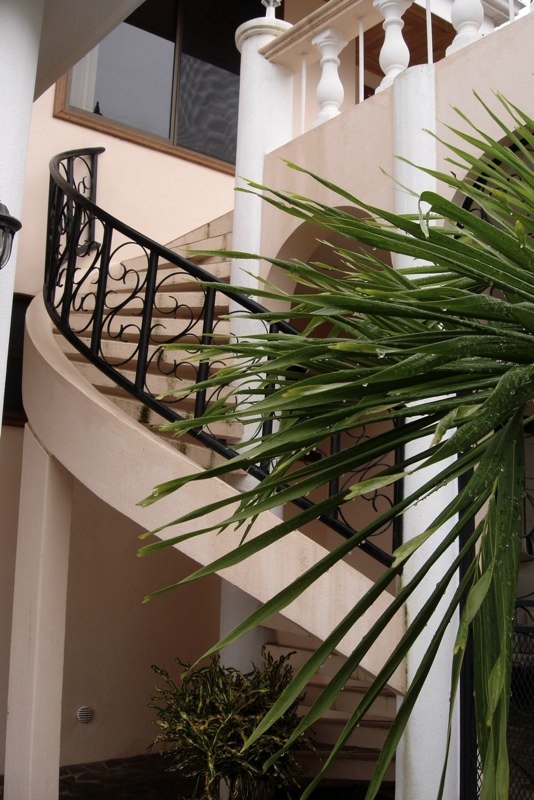 Staircase leading to a large secondary balcony with table and chairs.