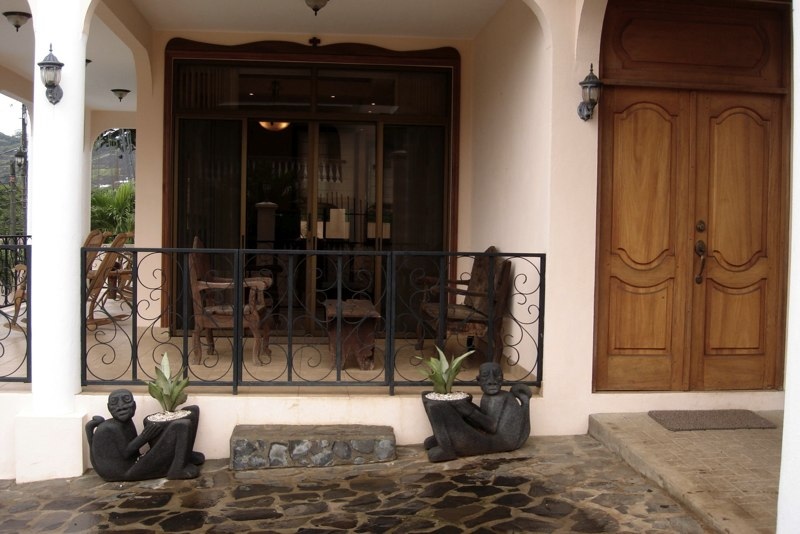 Villa's entrance adjacent to the wrap-around porch and outdoor seating nook.