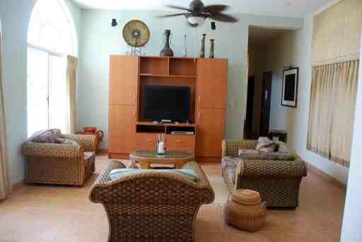 Fully furnished living room with flat-screen TV.