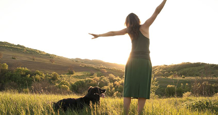 A image of a young women and a black dog facing to sun set