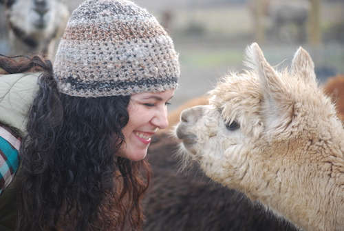 Sara, wearing a handmade alpaca hat, touching noses with Caroline, the alpacar