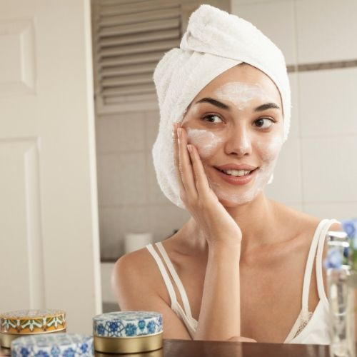 Woman applying skincare products to face