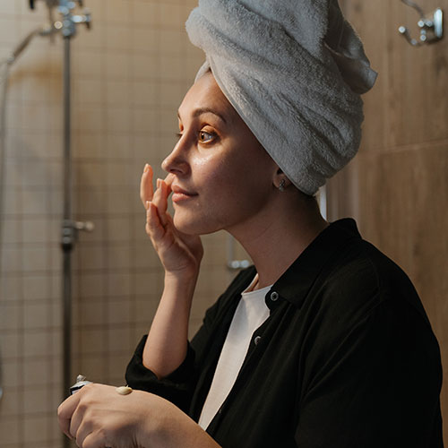 Woman treating dry skin with cream