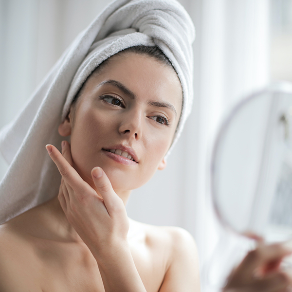 Woman exfoliating face during skin care routine