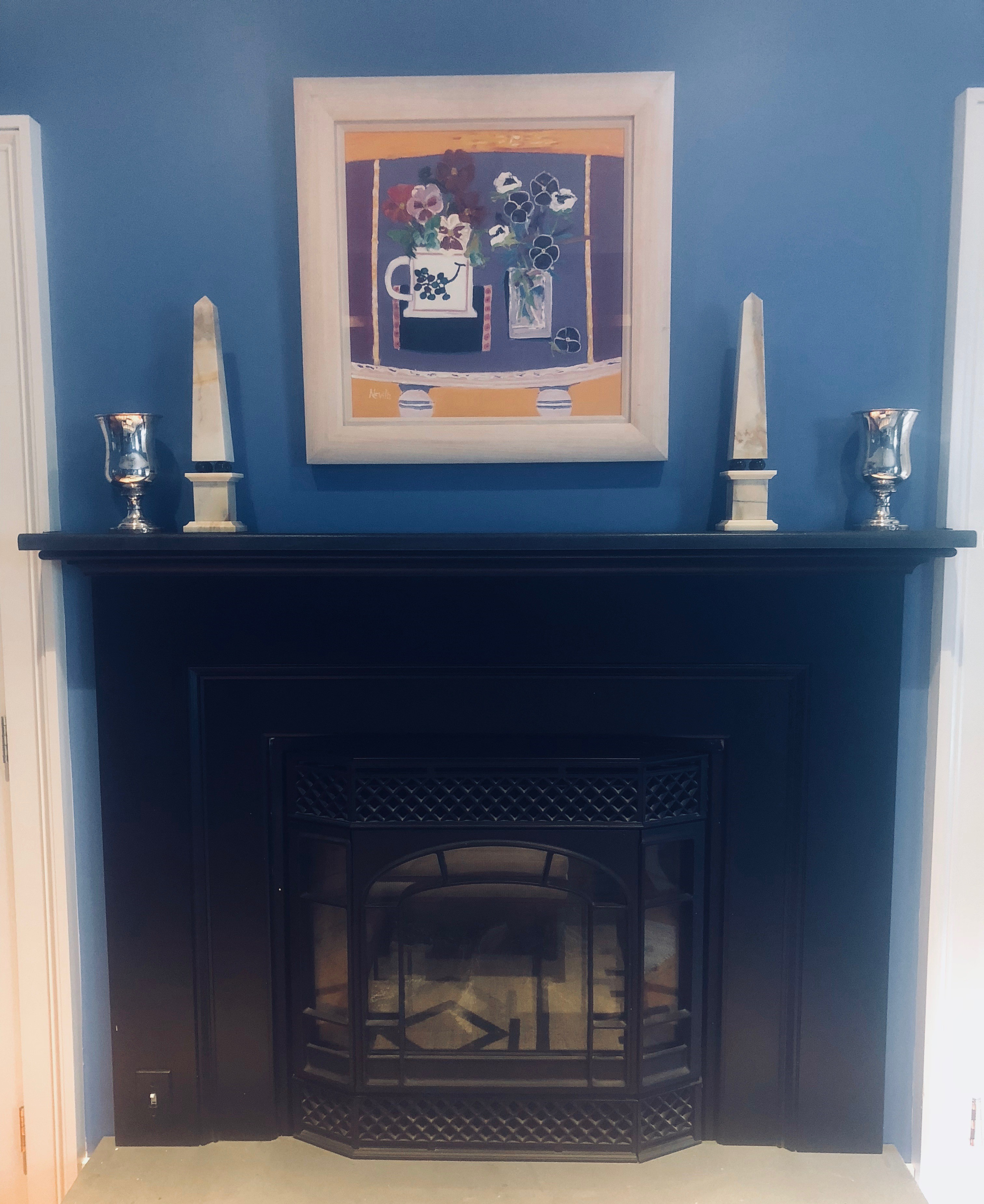 painting above fireplace with pair of obelisks